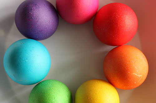 seven colored eggs on a plate